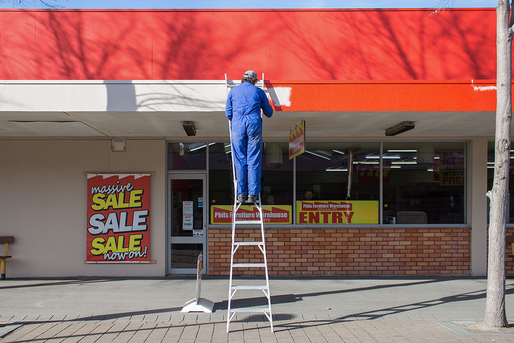 Thumbnail Image of Man on ladder painting outside of furniture store